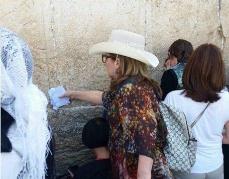 אישה מבוגרת מכניסה פתק לקיר כותל